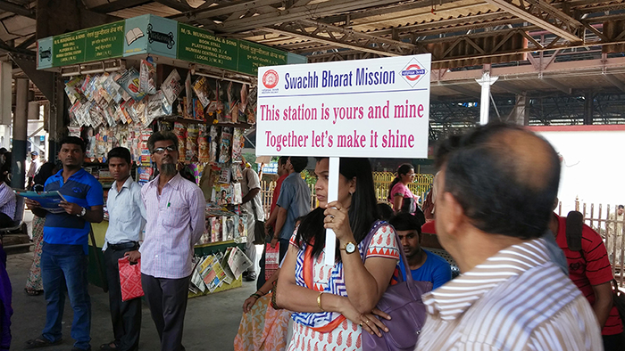 A railway employee holding the Swachh Bharat hoarding