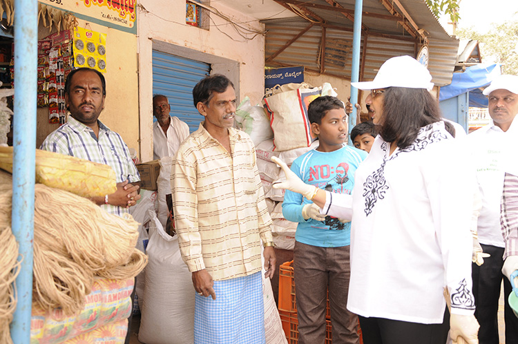 Biocon Chairperson and Managing Director Kiran Mazumdar-Shaw interacts with residents and shopkeepers in Huskur village to spread awareness on the need to keep their surroundings clean